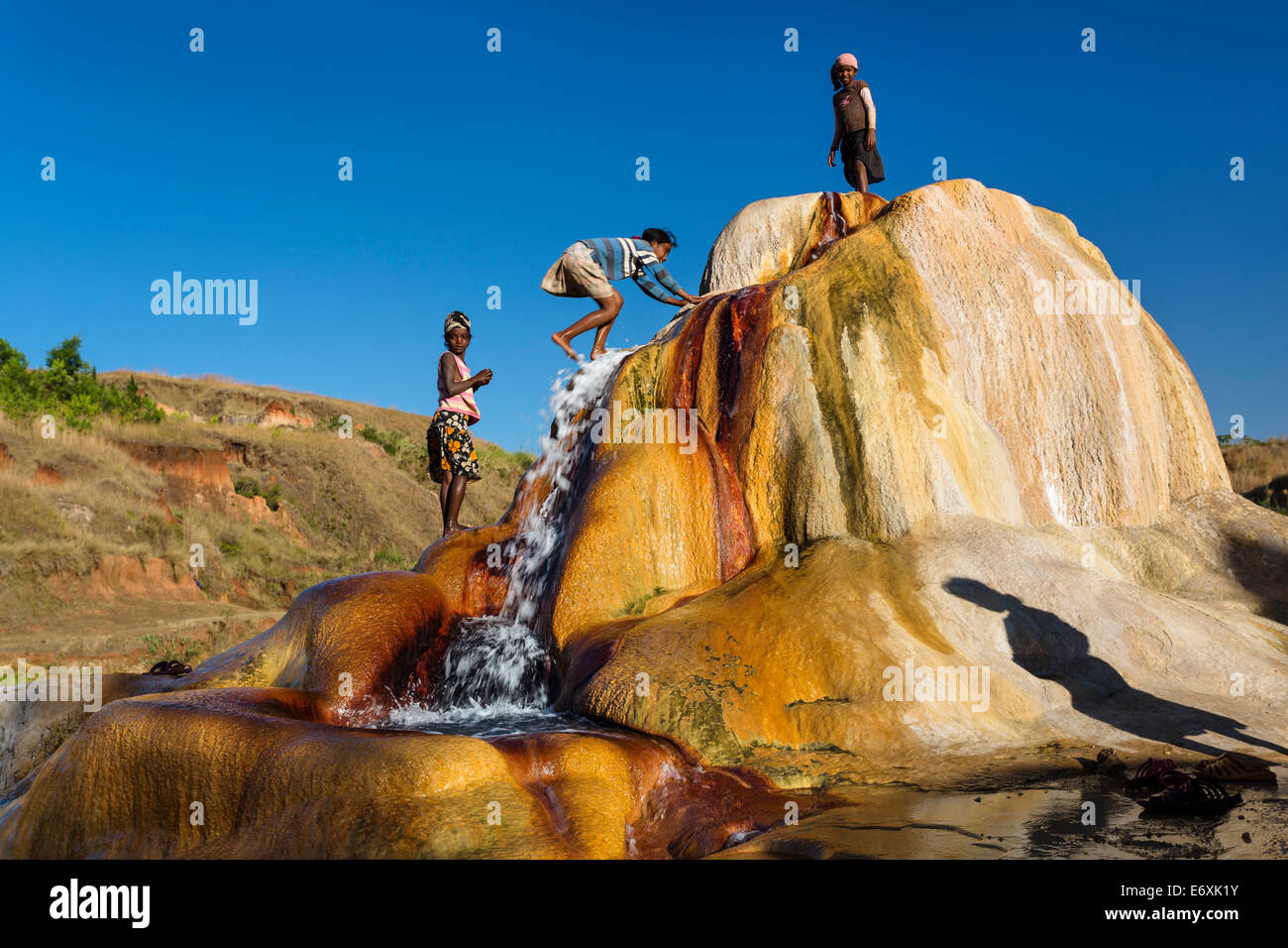 Madagascan children playing in a spouting Geyser, Geysers of Ampefy, highlands, Madagascar, Africa - Stock Image