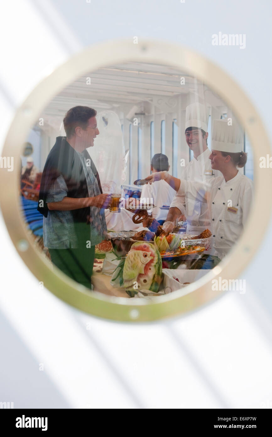 Cheerful chefs serving hearty delicacies during pre-lunch drinks on the the pool deck of cruise ship MS Deutschland - Stock Image