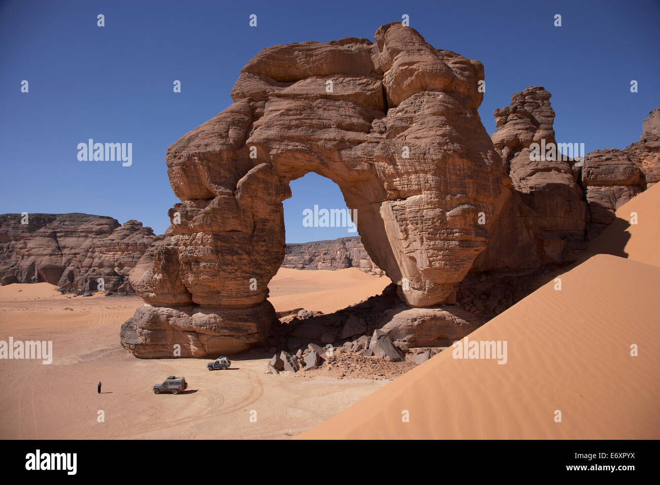 Off-road vehicles near a natural arch, Tadrart Acacus, Ghat District, Lybia - Stock Image