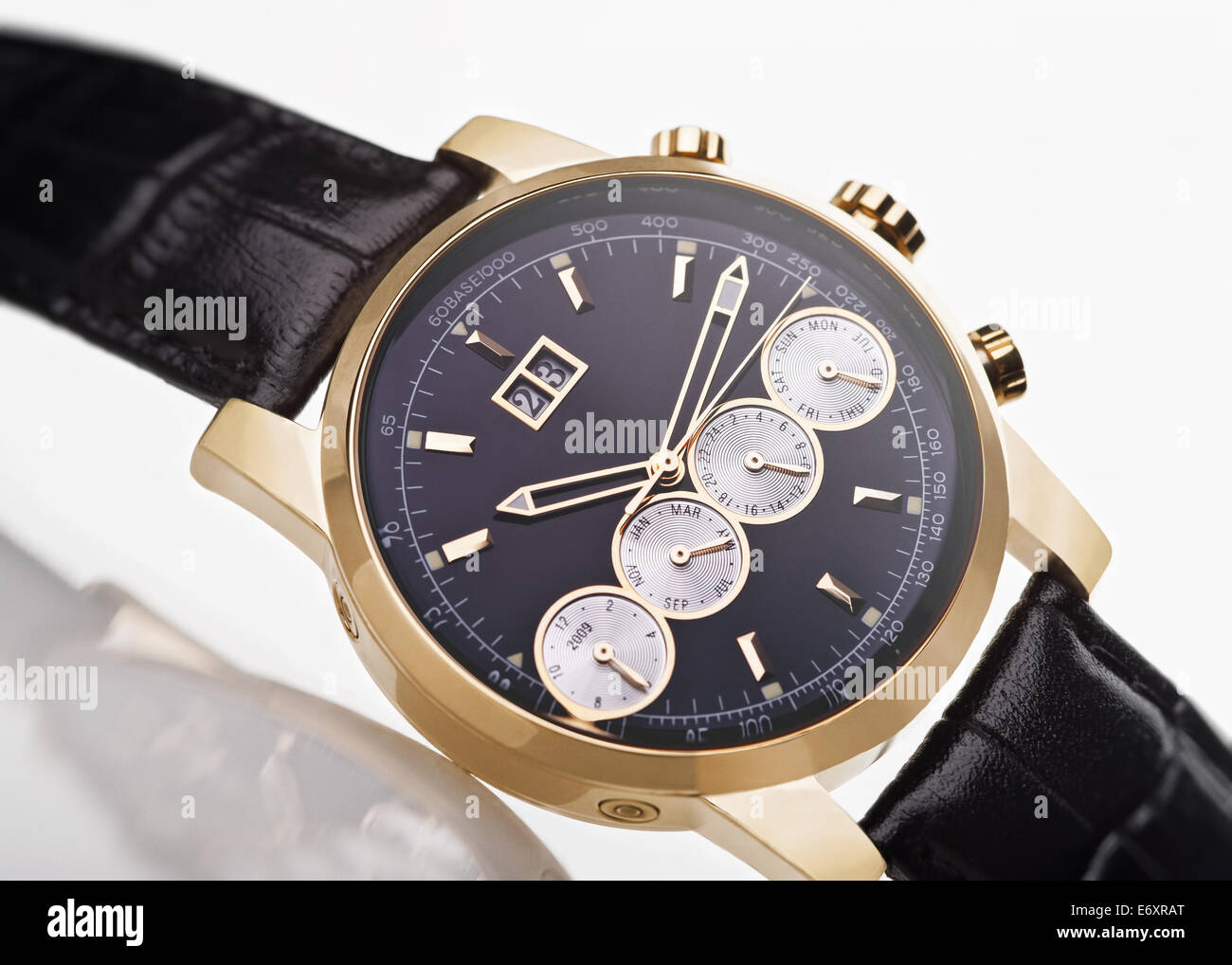 gold men's wristwatch with black leather strap on a white background - Stock Image