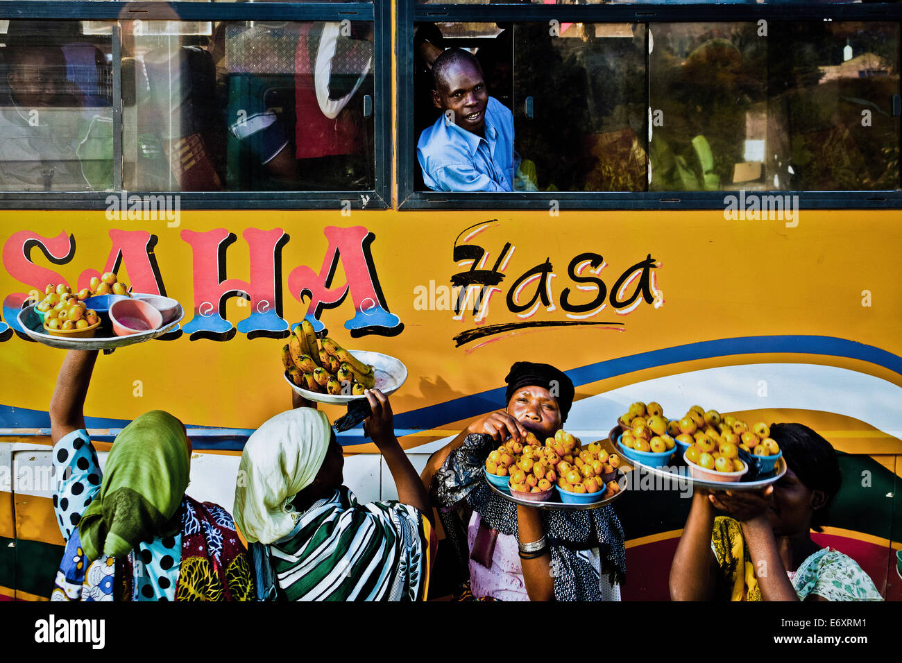 Women selling fruit to bus travellers, Tanzania, Africa - Stock Image
