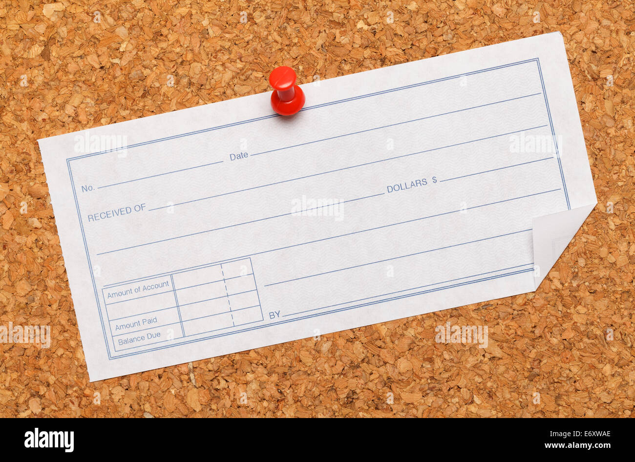 Cork Board with receipt taced on it. - Stock Image