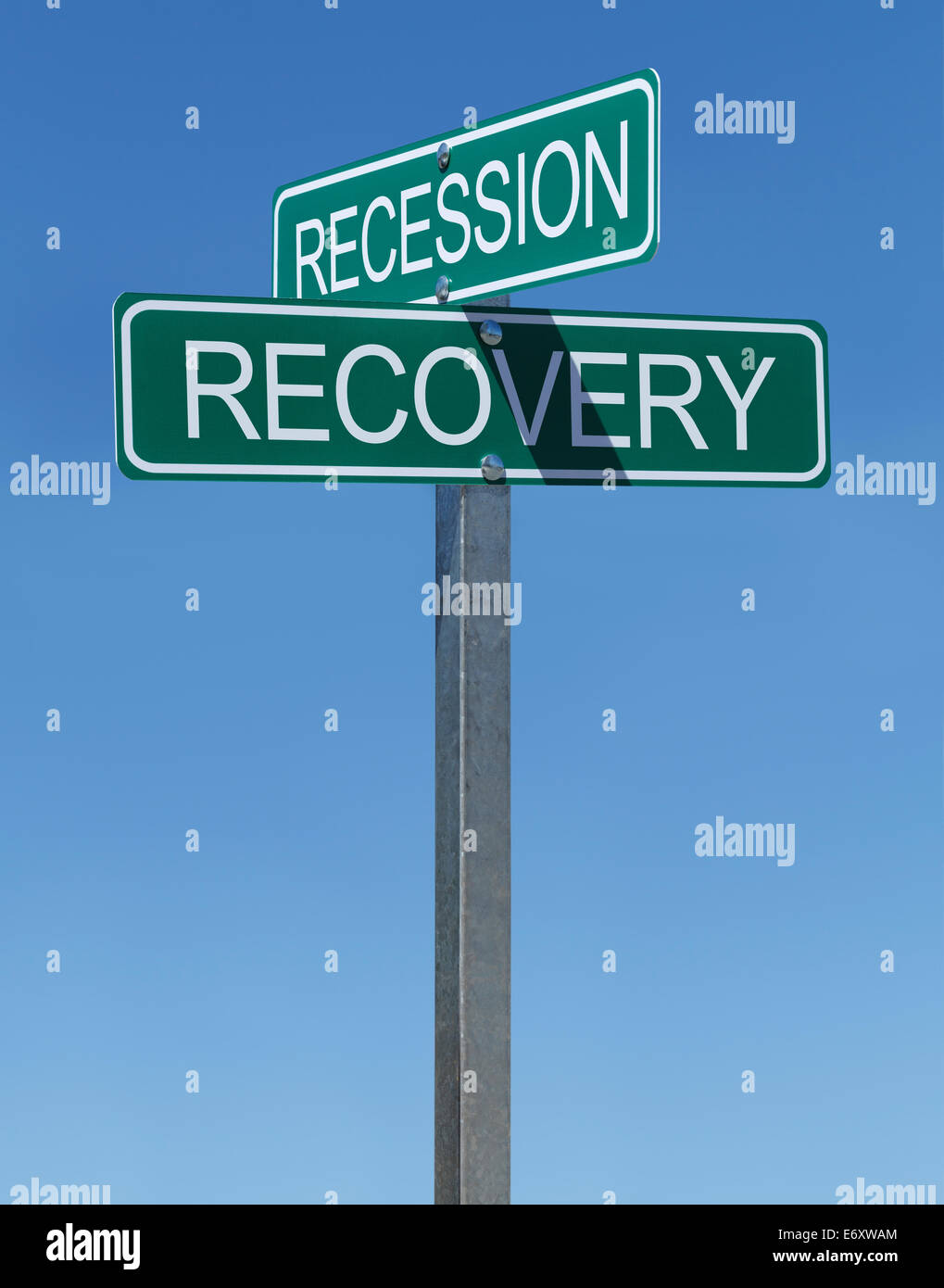 Two Green Street Signs Recession and Recovery on Metal Pole with Blue Sky Background. - Stock Image