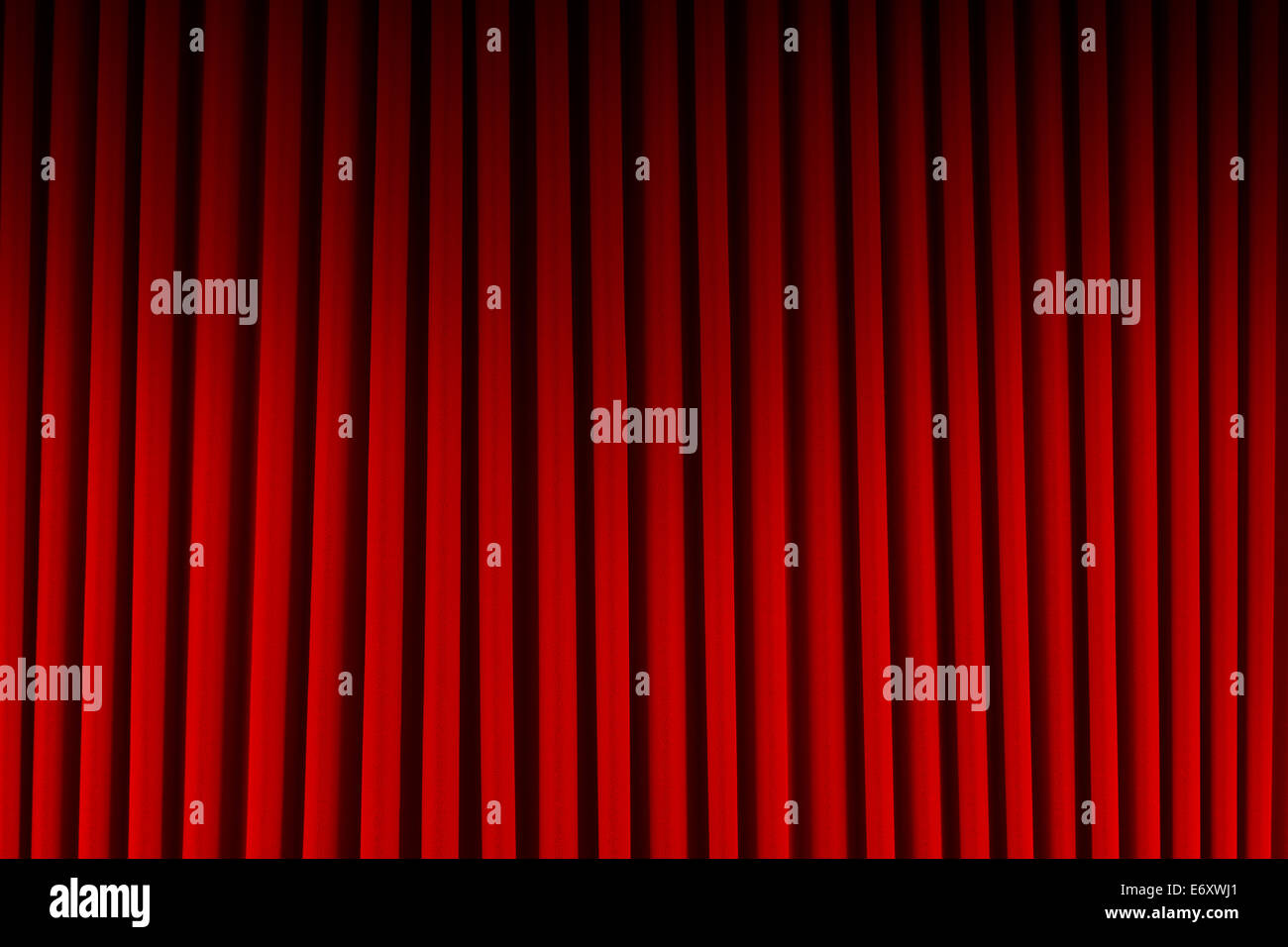 Red Velvet Stage Curtains Dim Lit Background. - Stock Image