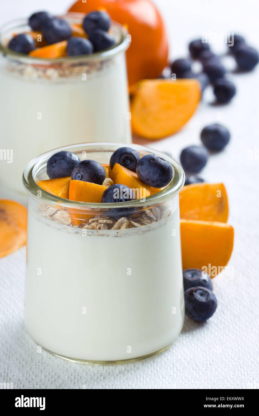 Jars of yogurt topped with blueberries and persimmon pieces - Stock Image