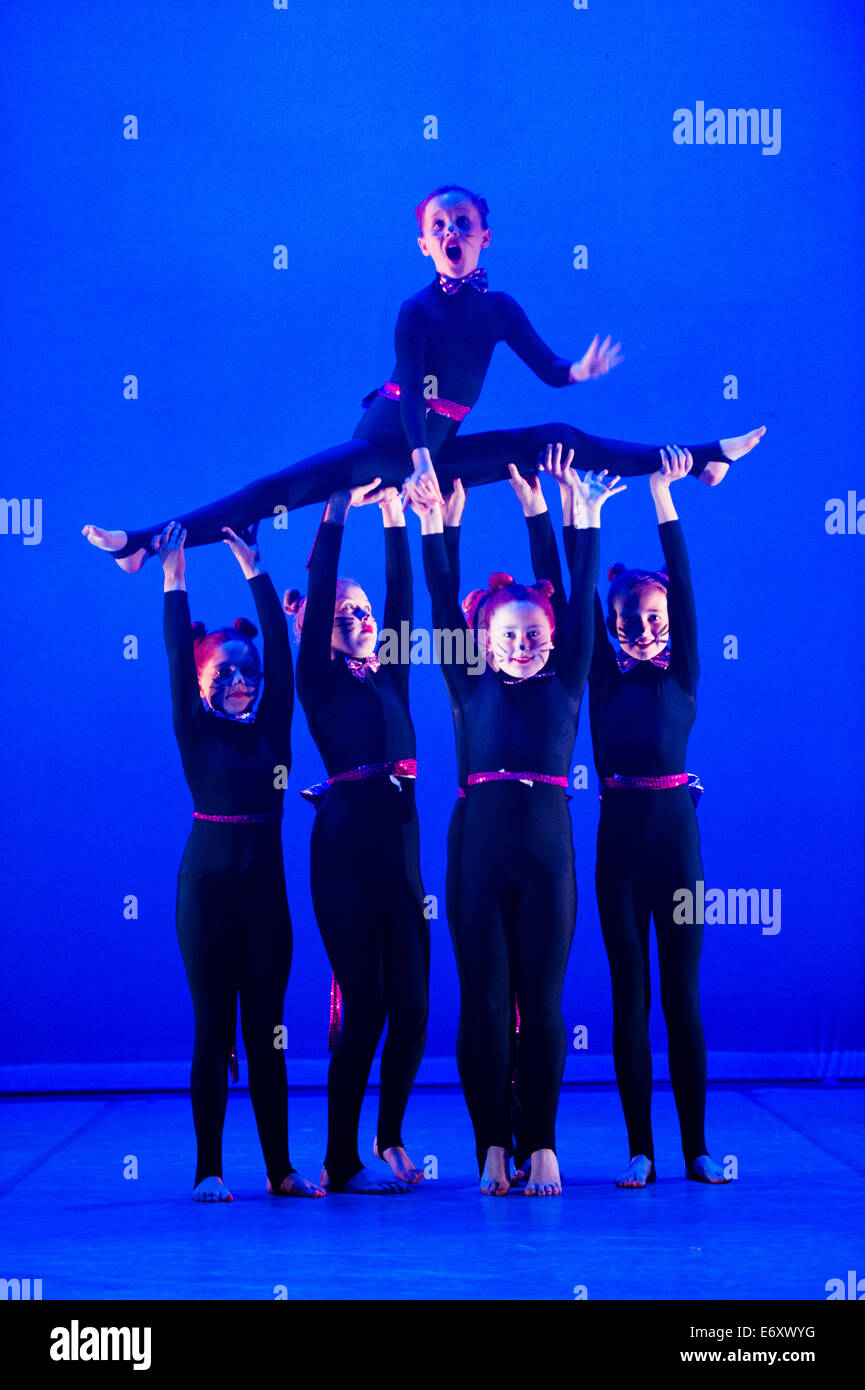 Pre-teen girls dancing on stage in a dance school showcase performance Aberystwyth Arts Centre Wales UK - Stock Image