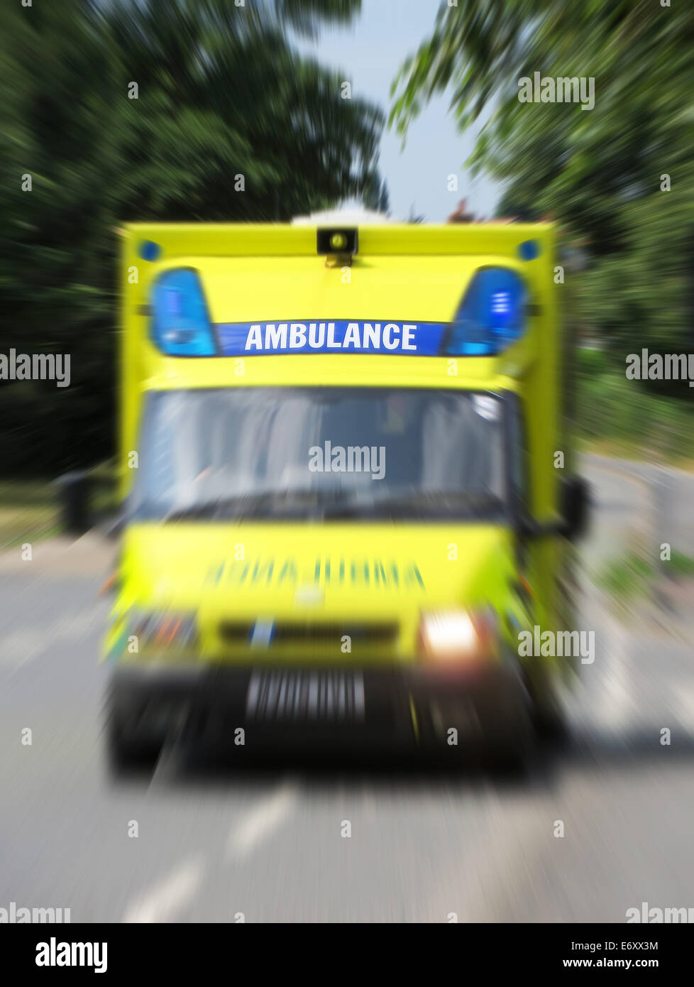 Ambulance in road with zoom effect focusing on sign. - Stock Image