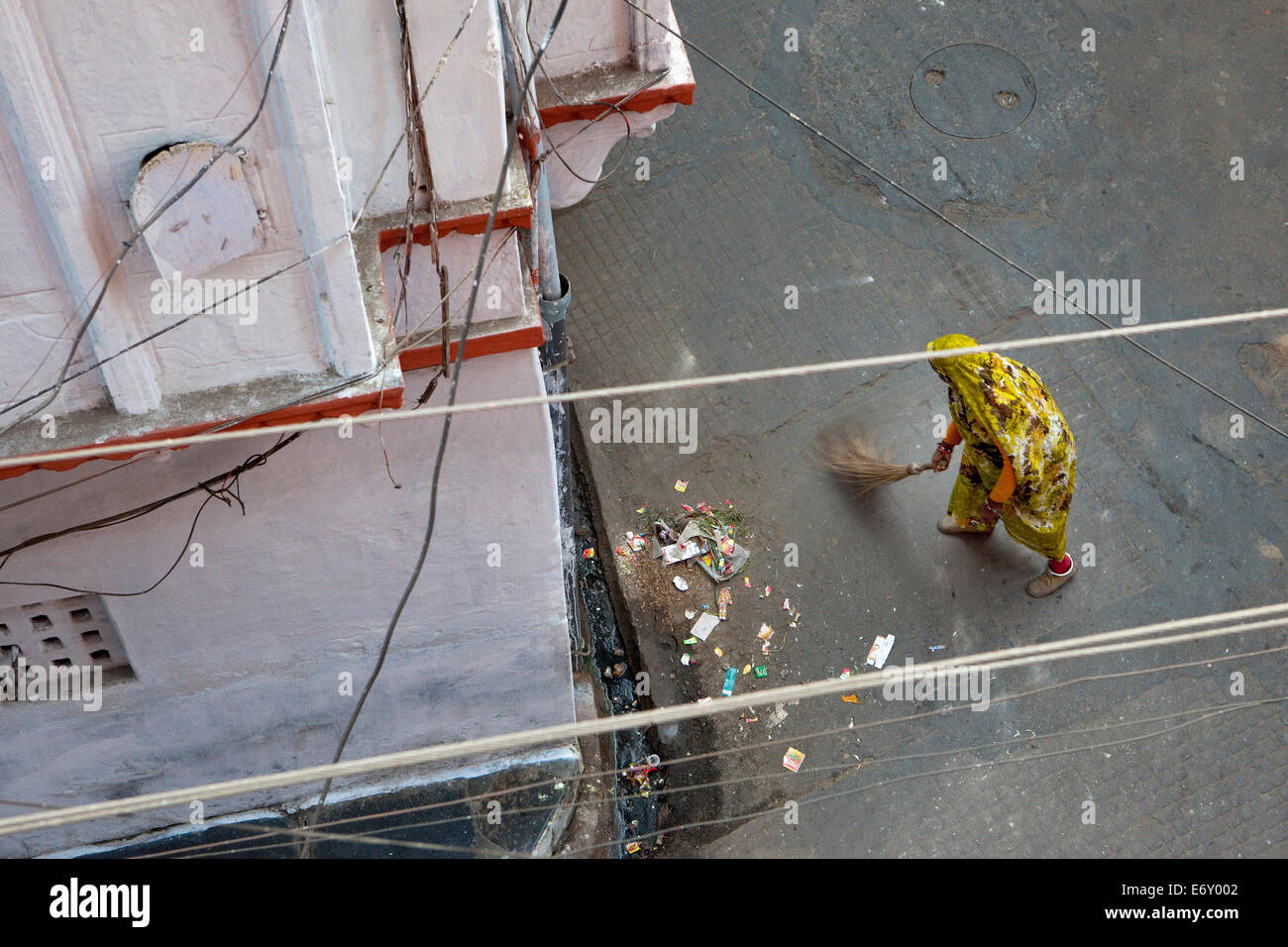 View from above to woman wearing a sari and sweeping the street, Udaipur, Rajasthan, India - Stock Image
