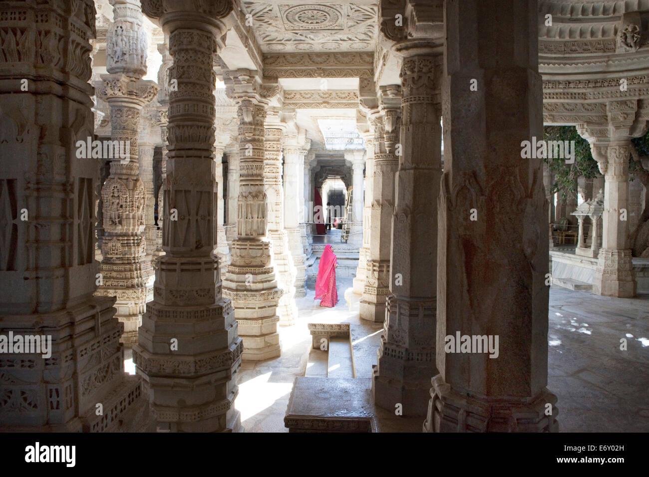 Indian woman wearing sari between the pillars of the jainist main temple Chaumukha Mandir, Ranakpur, Rajasthan, - Stock Image