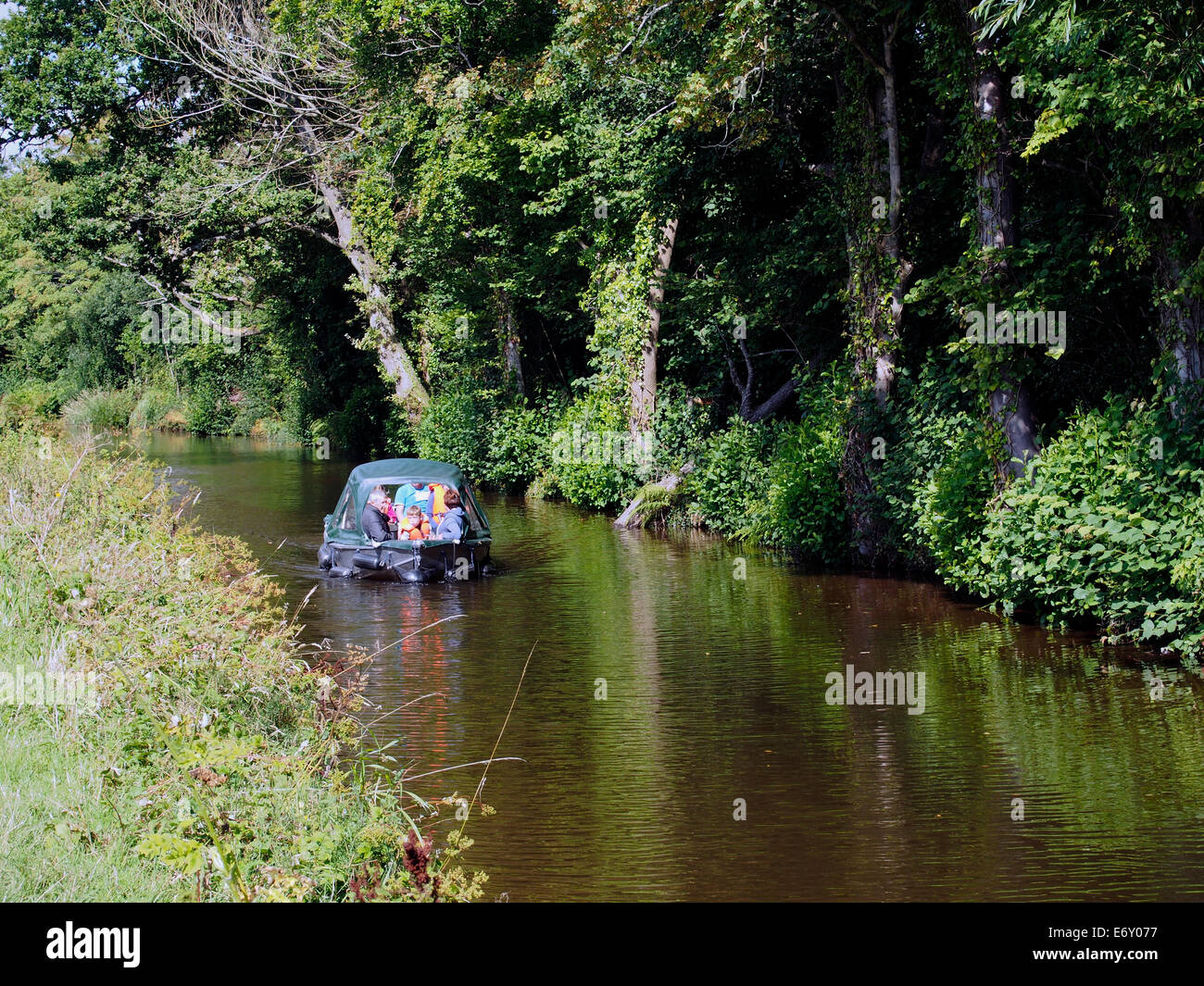 The Monmouthshire & Brecon Canal (Mon & Brec) on the edge of Brecon with a small day boat approaching. - Stock Image