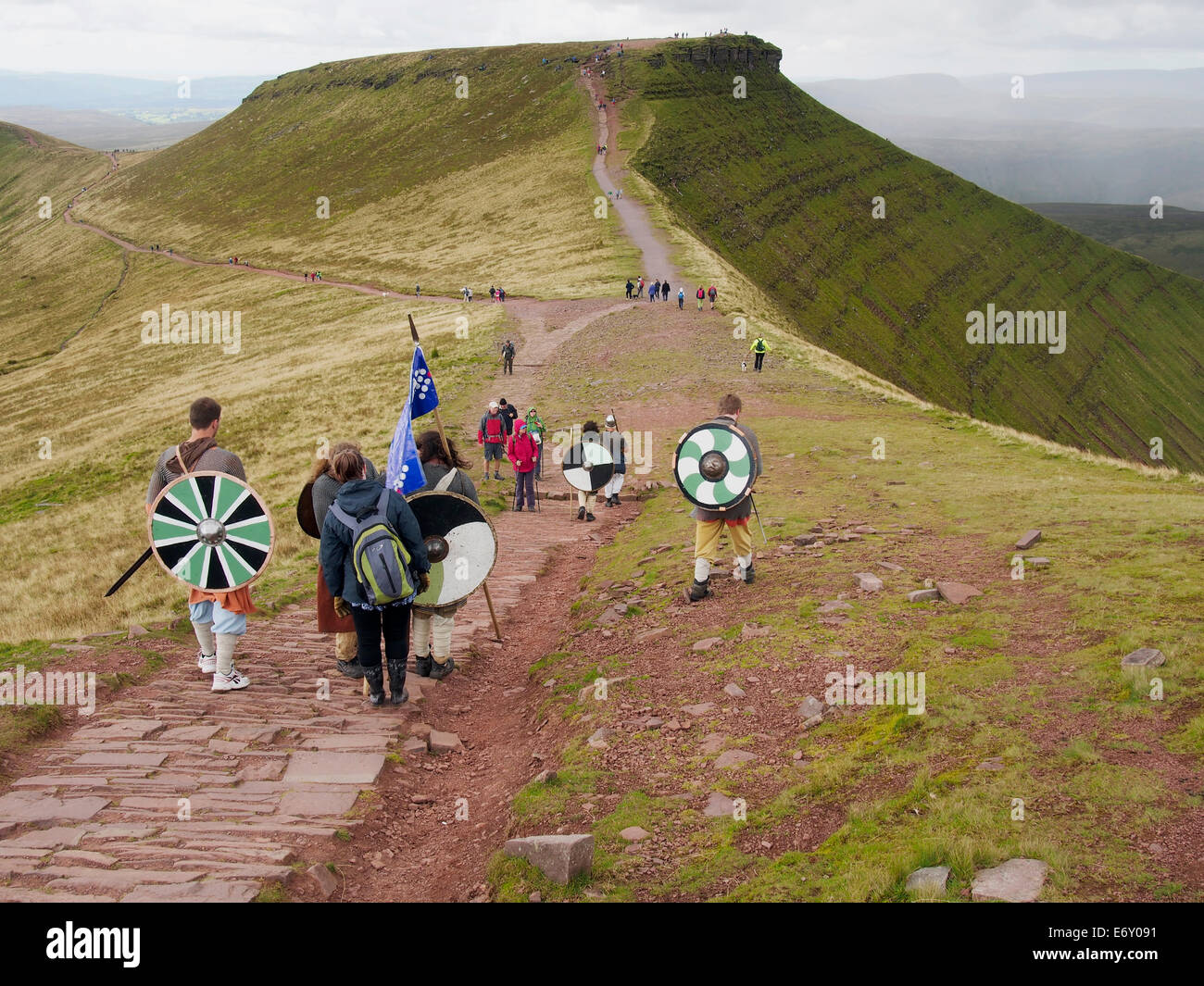 Hill walking on the Brecon Beacons. A group of charity walkers in Celtic dress on the footpath from Pen y Fan with - Stock Image