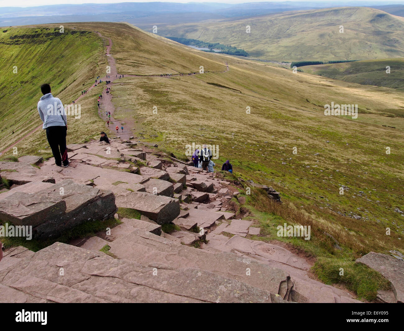 Hill walking on the Brecon Beacons. Walkers on the main trail from car park near Storey Arms head for the summit - Stock Image
