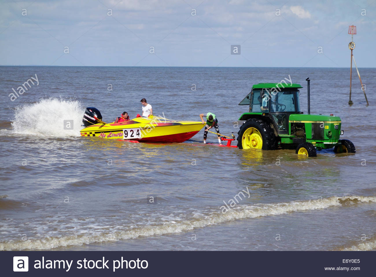 Tractor and trailer recovering a boat from the sea at Hunstanton - Stock Image