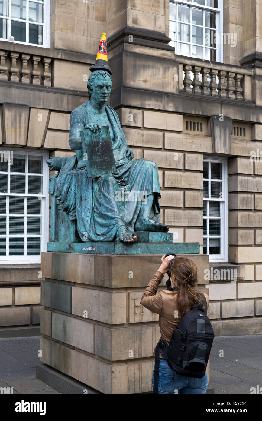 """A young woman photographs the statue of David Hume with """"No Parking"""" cone on his head on the Royal Mile, Edinburgh, Stock Photo"""