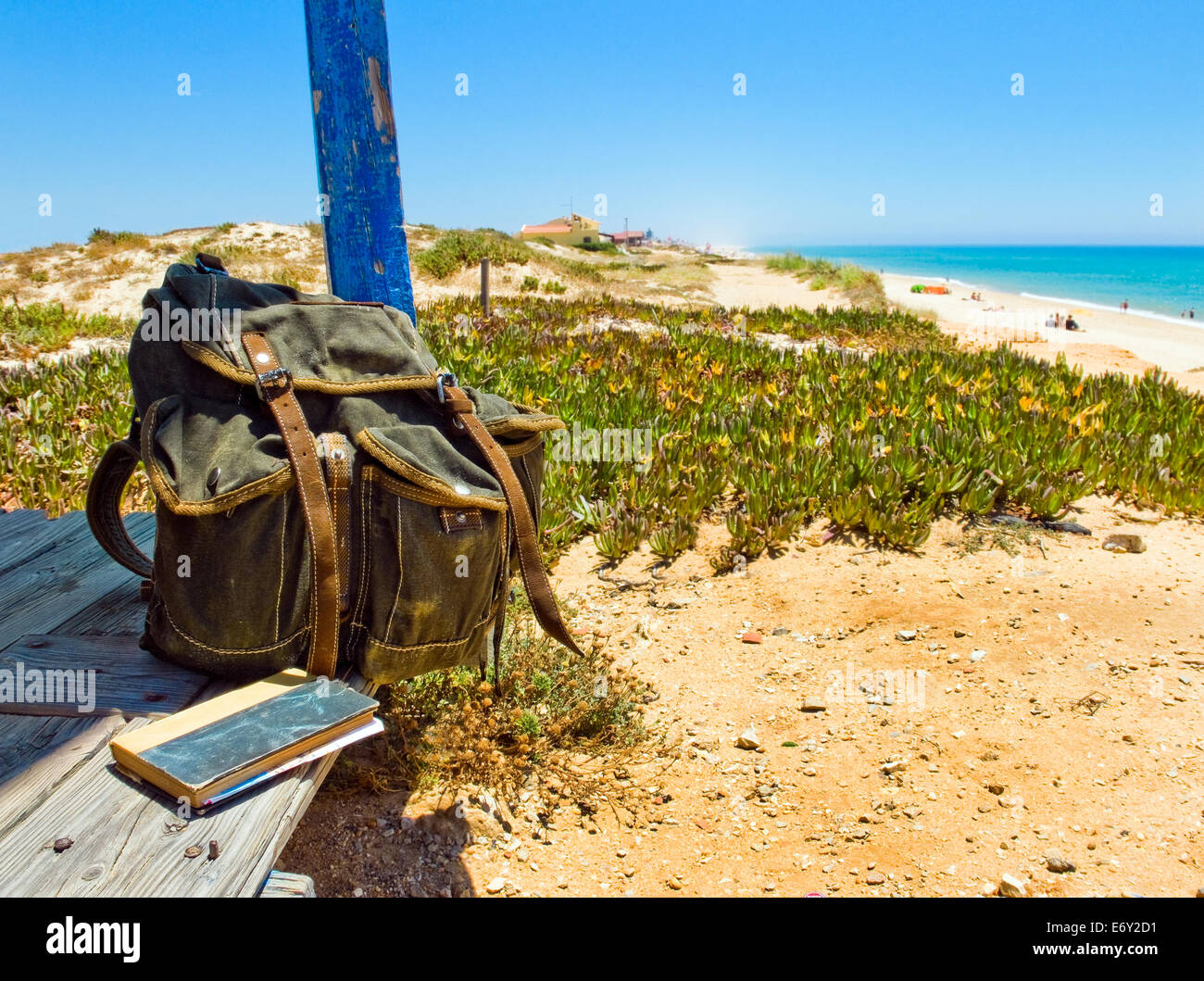 Backpack and book on the porch of a wooden hut next to the shore of a European beach. Backpacking traveller taking - Stock Image
