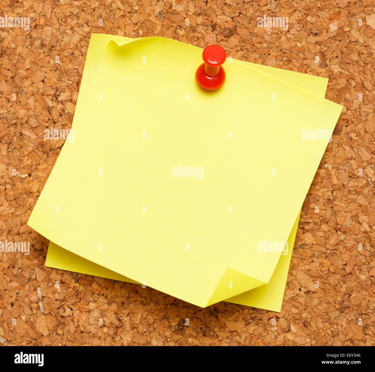 Two blank yellow sticky notes pinned onto cork board. - Stock Image