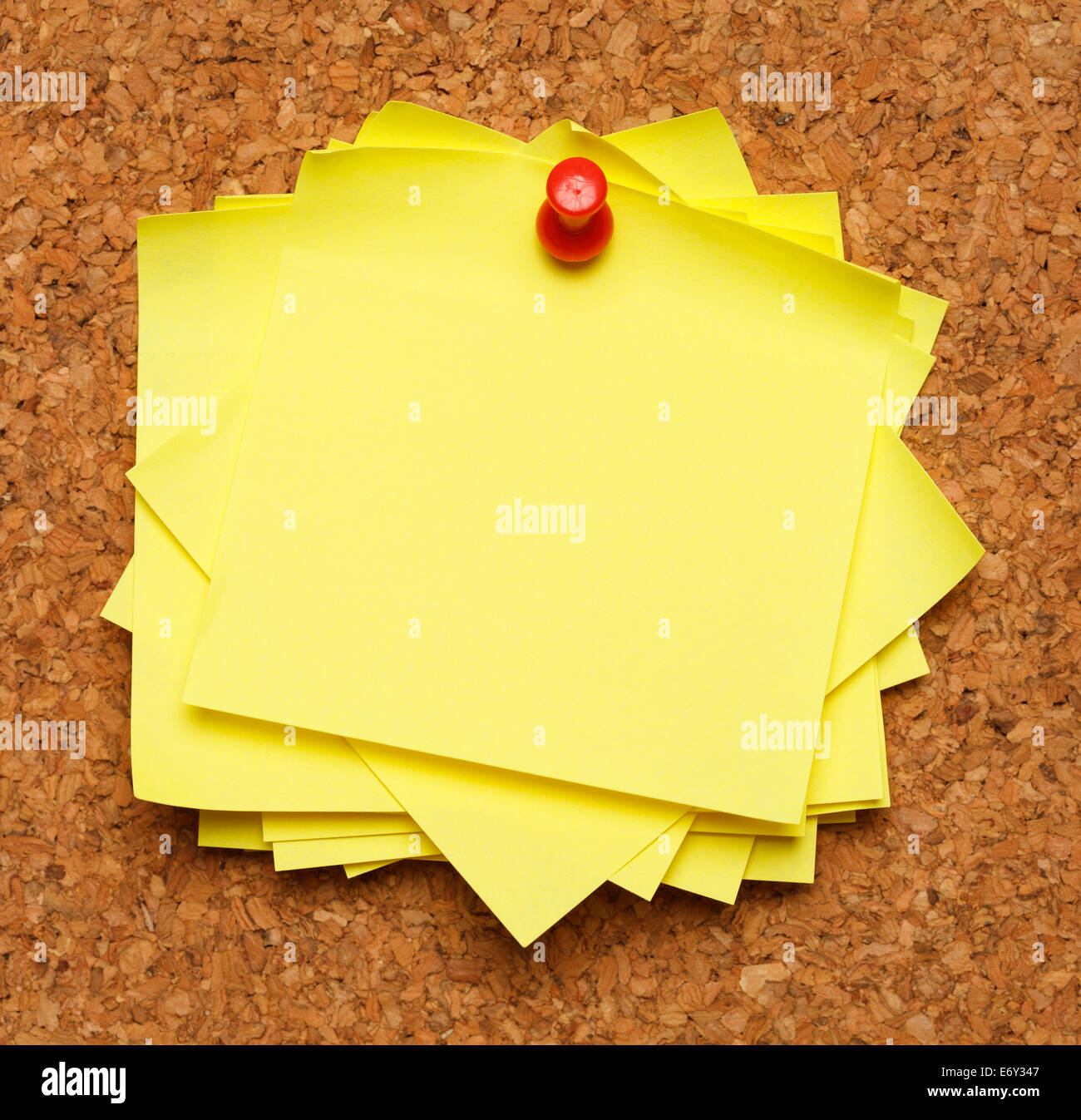 Bunch of sticky notes tacked to cork board. - Stock Image