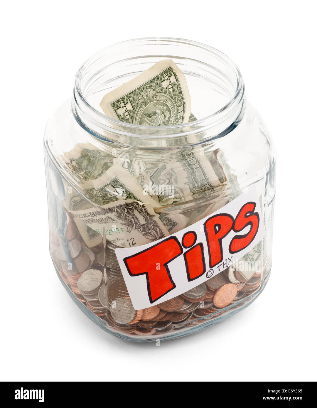 Glass Jar half full of money with a tips label on it, isolated on a white background with drop shadow. - Stock Image