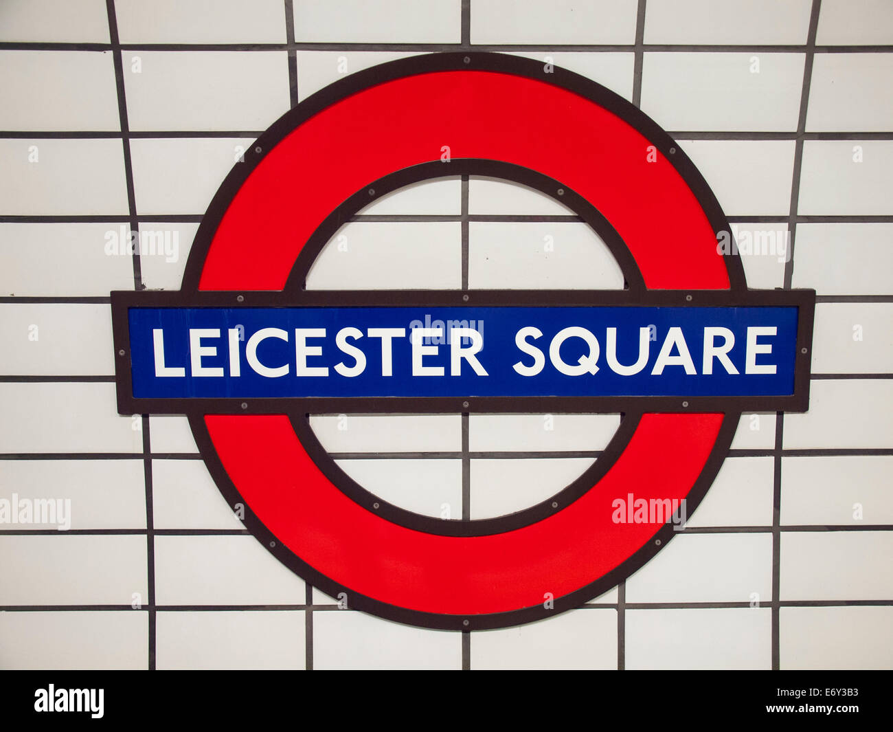 london underground symbol for leicester square station against  white tiled wall - Stock Image