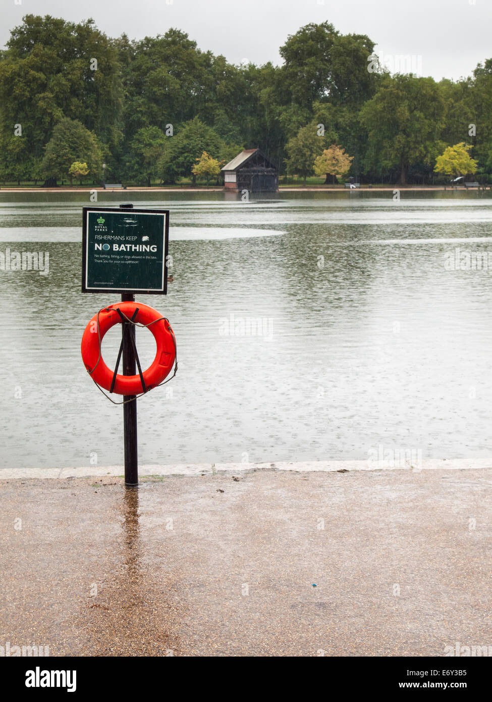 the serpentine boating lake hyde park in heavy rain with no bathing sign and life belt in foreground and boat shed - Stock Image