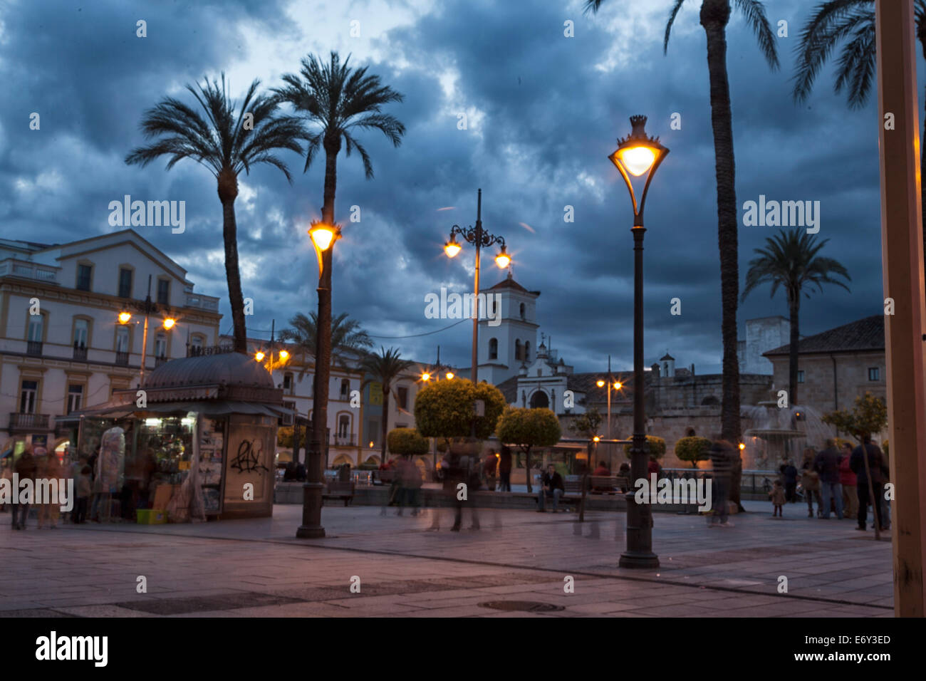 People walk and play in the Plaza Mayor of Merida Spain during the evening hours and the street lights come on. - Stock Image
