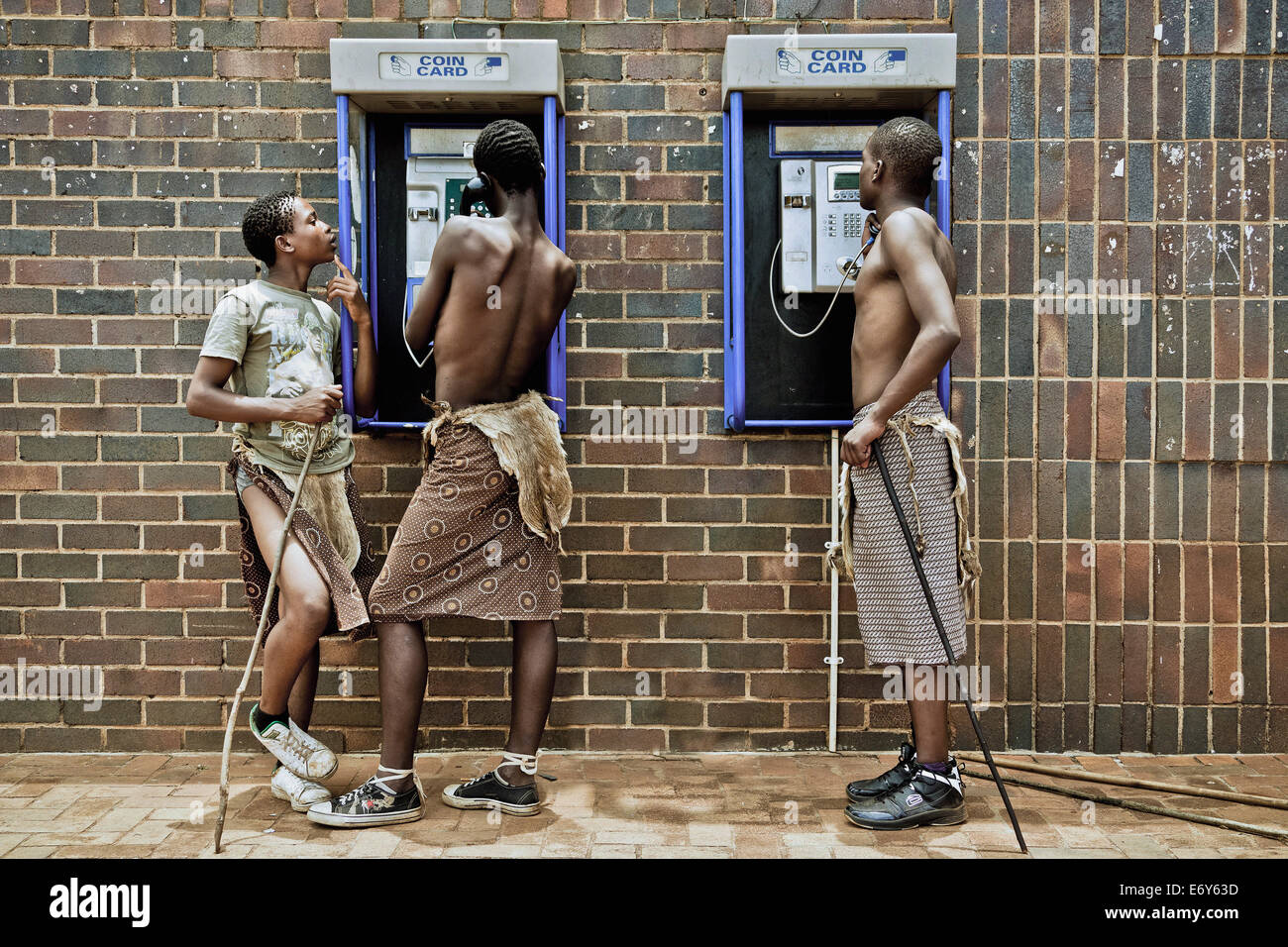 Three young men of the Swazi tribe at a telephone booth wearing traditional clothes, Swaziland, Africa Stock Photo