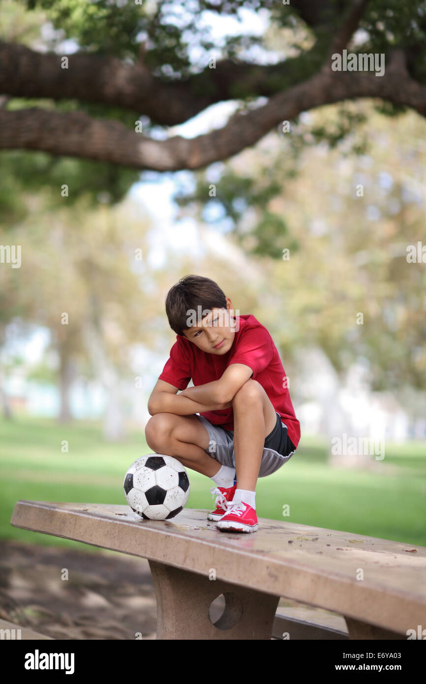 Young boy in the park on a table with football - Stock Image