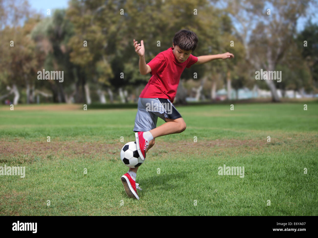 Young boy plays with a soccer ball practicing kicks - authentic action - Stock Image