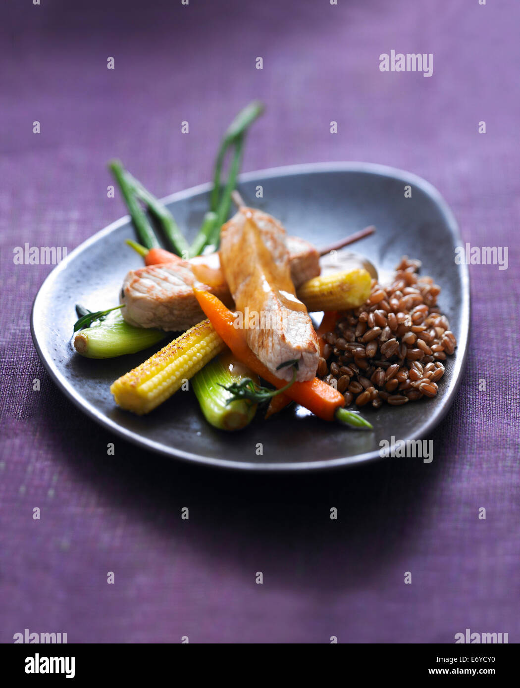 Veal saddle savory brochettes,stewed spelt and glazed mini vegetables - Stock Image
