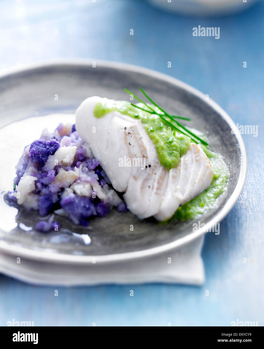 Piece of cod with creamy chive sauce,purple potato and celeriac mash - Stock Image