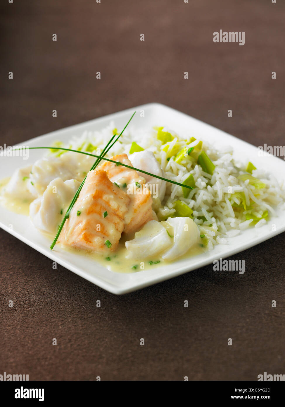 Three varieties of fish in white sauce,basmati rice with leeks - Stock Image