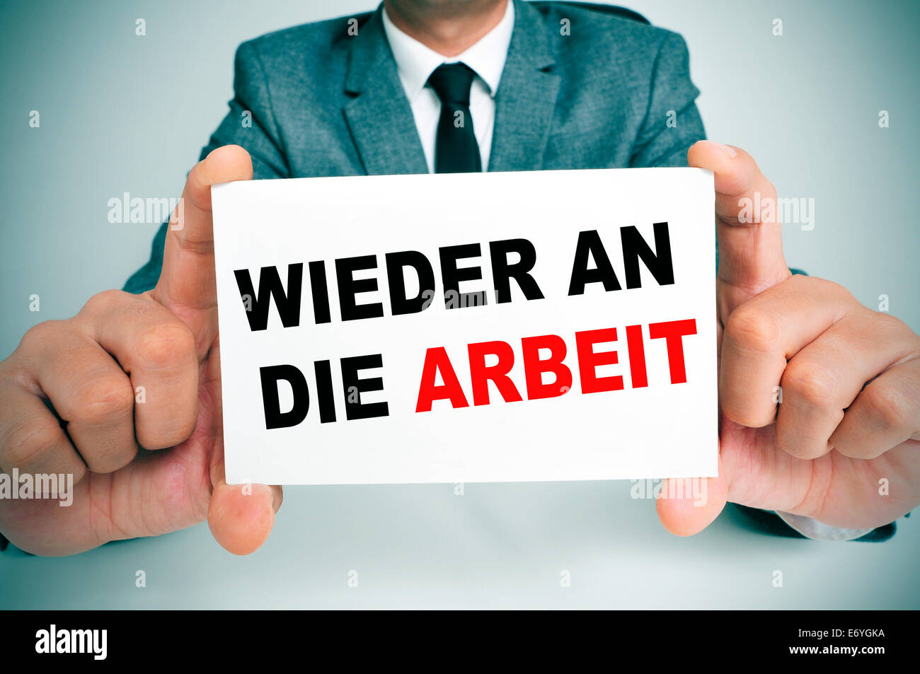 businessman holding a signboard with the text wieder an die arbeit, back to work in german, written in it - Stock Image