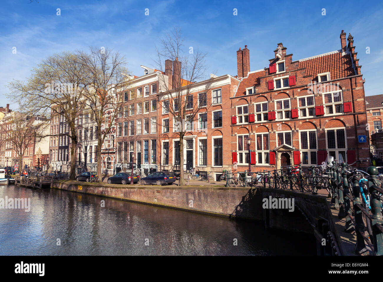 AMSTERDAM, NETHERLANDS - MARCH 19, 2014: Colorful houses along the canal embankment in spring day. Ordinary people - Stock Image