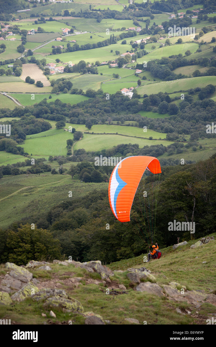 At the Baïgoura summit (2,942 feet), a paraglider ready for his takeoff (French Basque country - Aquitaine - France). Stock Photo