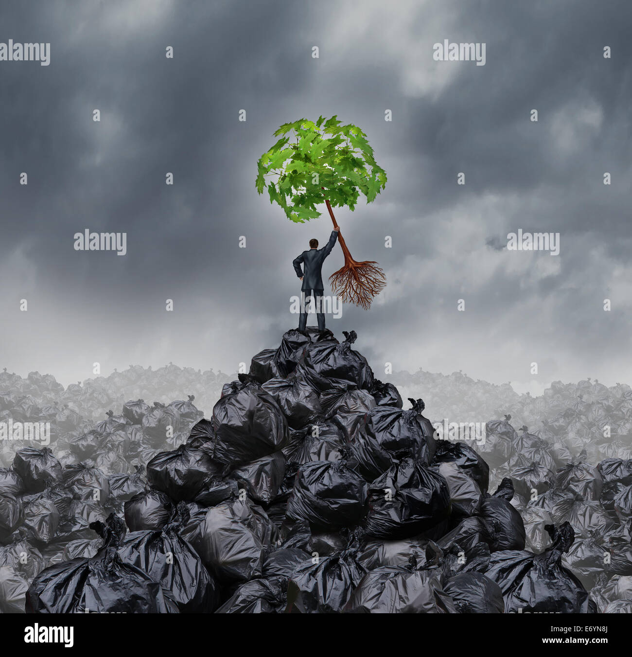 Green businessman concept as a man on top of a mountain heap of garbage holding up a green leaf tree with roots - Stock Image