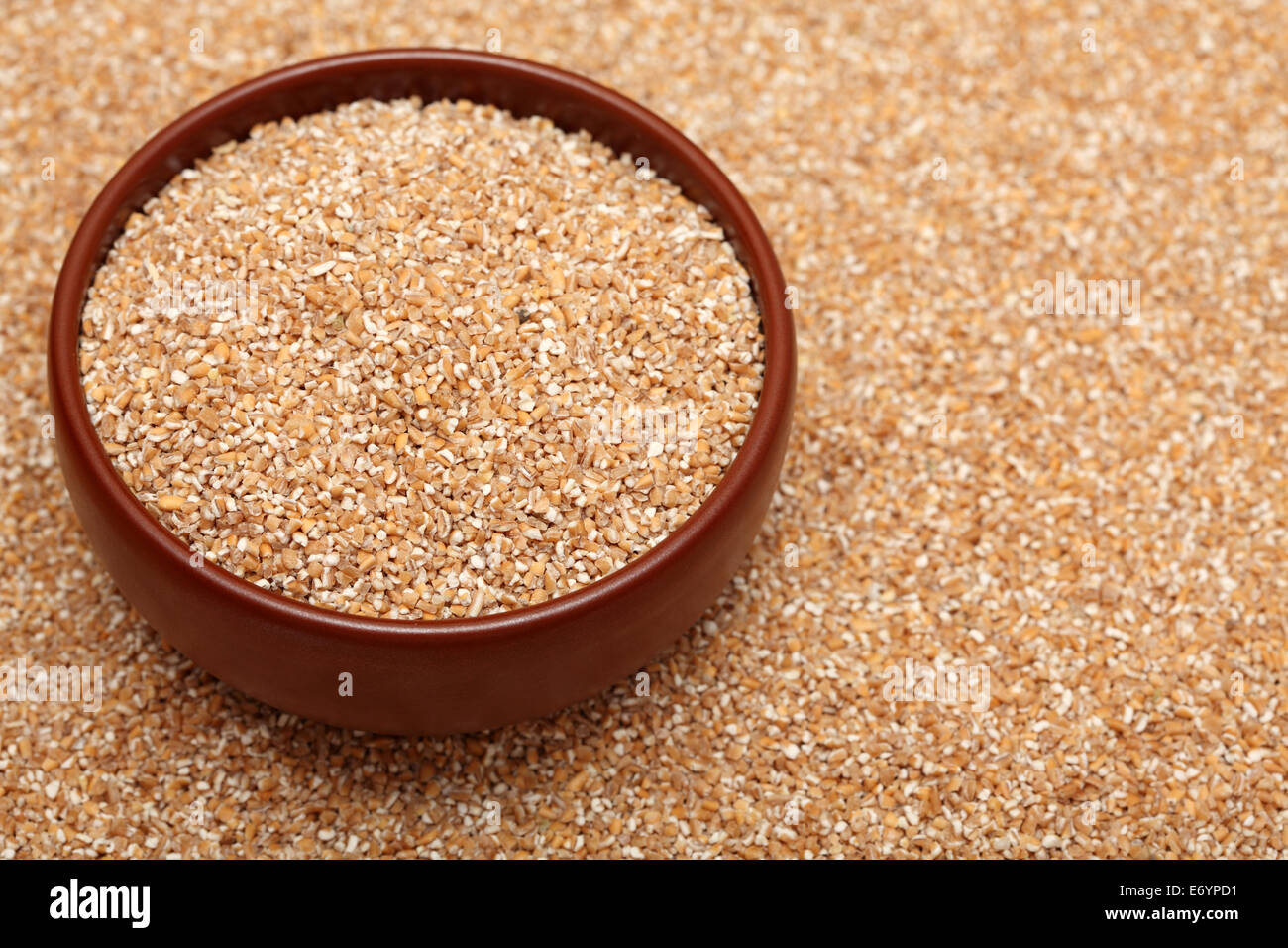 Wheat groats in bowl on wheat groats background. Closeup. - Stock Image