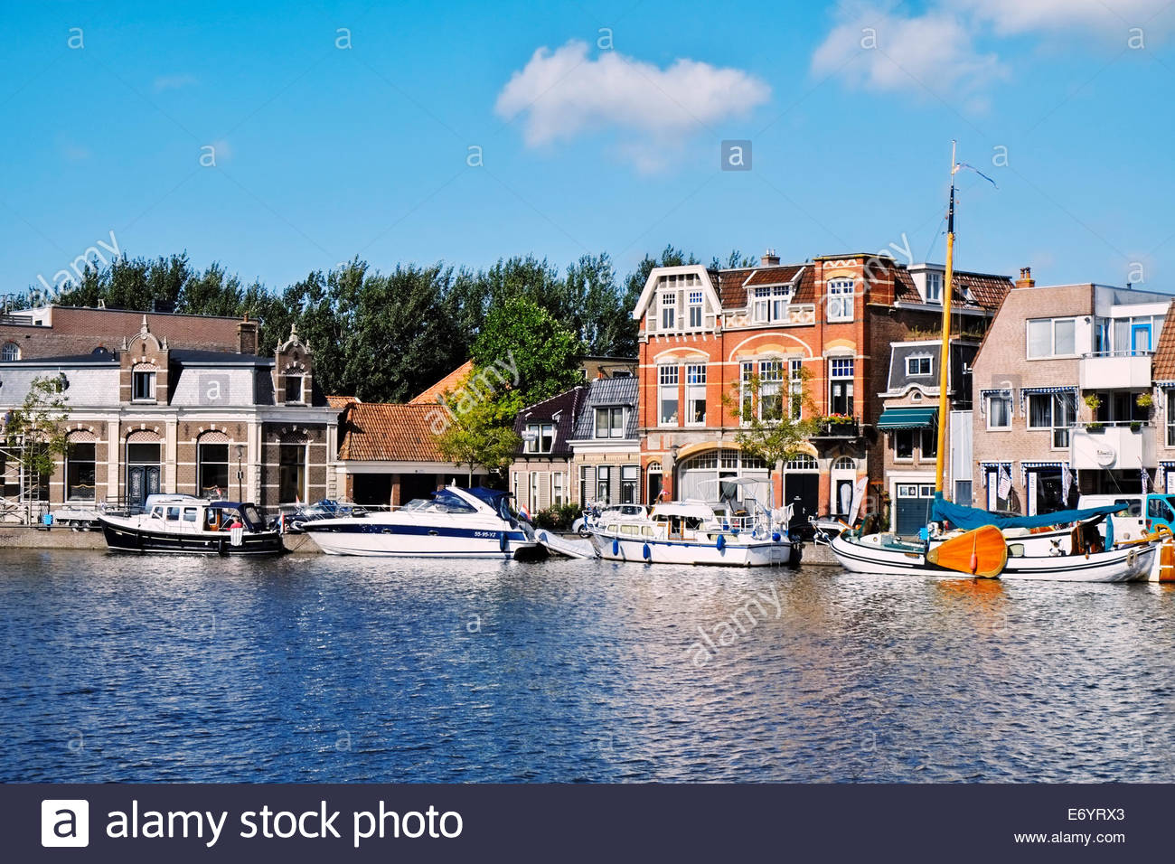 Houses and offices line the Geeuwkade leading to the Wonderbrug, with a variety of personal watercraft afloat in - Stock Image