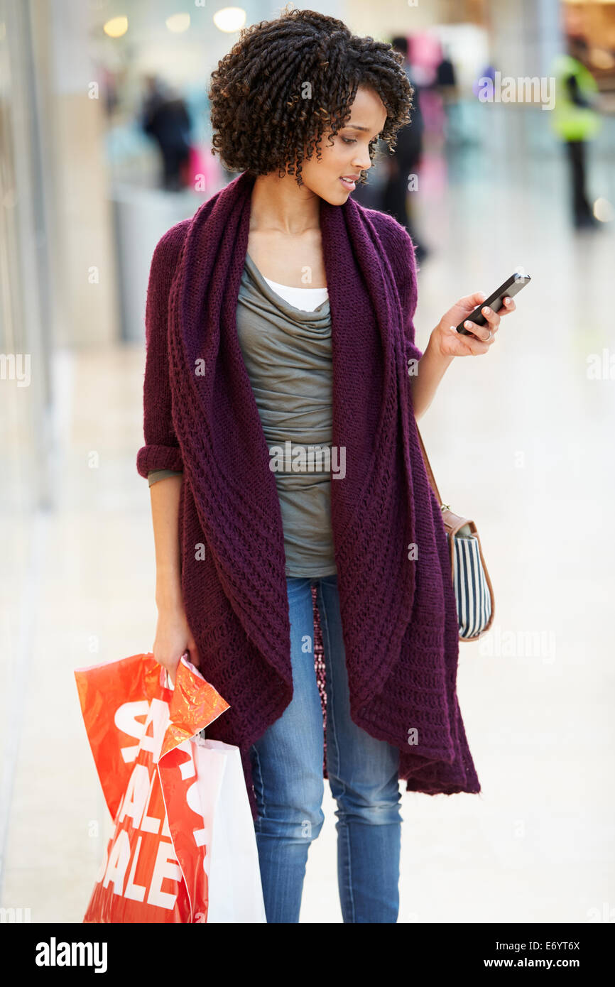 Woman In Shopping Mall Using Mobile Phone - Stock Image
