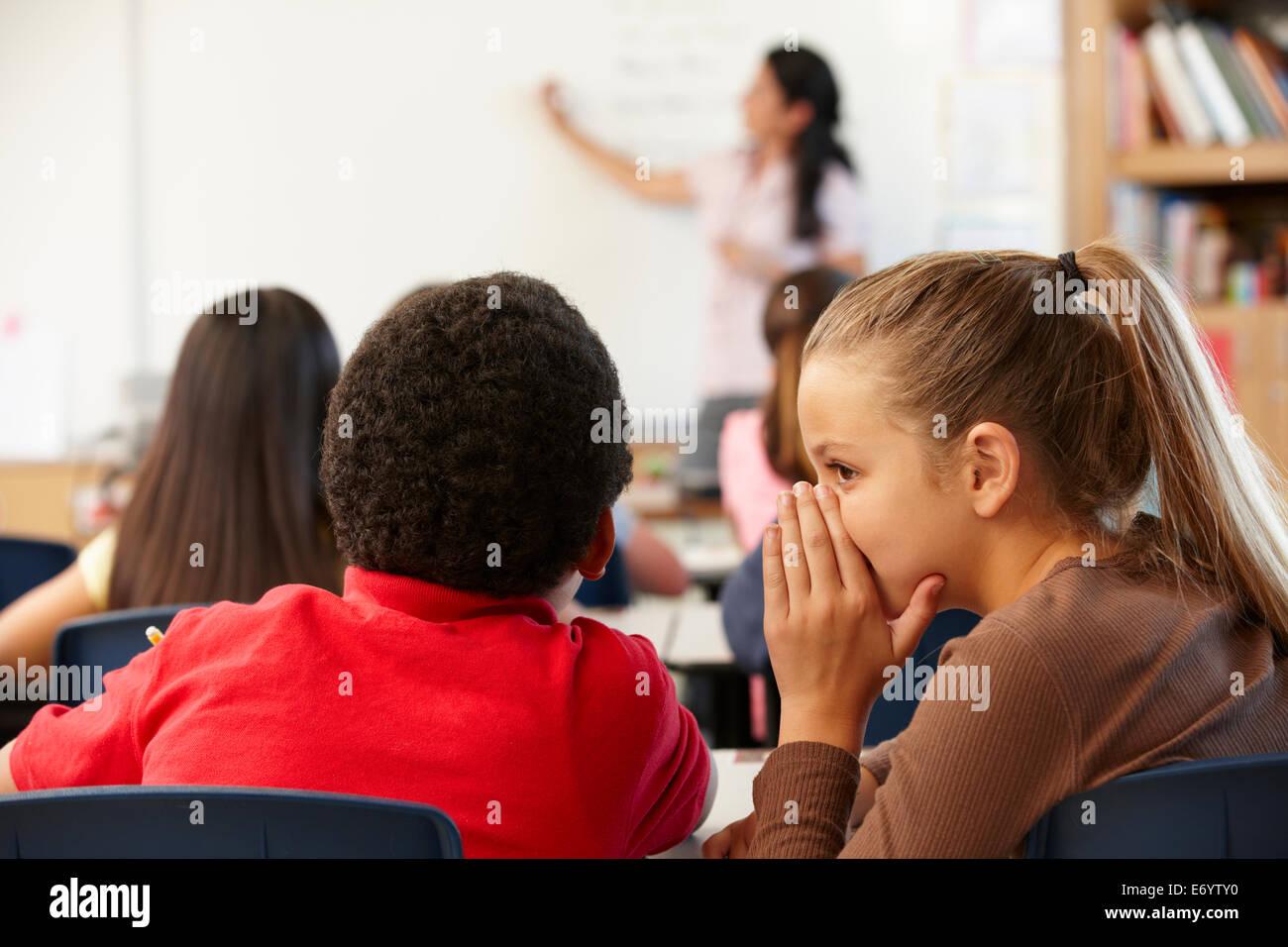 Schoolchildren whispering in class - Stock Image
