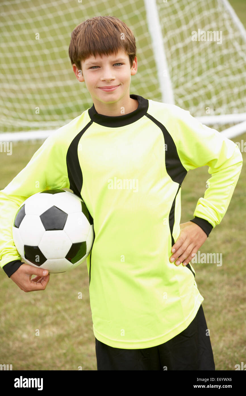 Portrait boy in goalkeeper's kit with ball - Stock Image