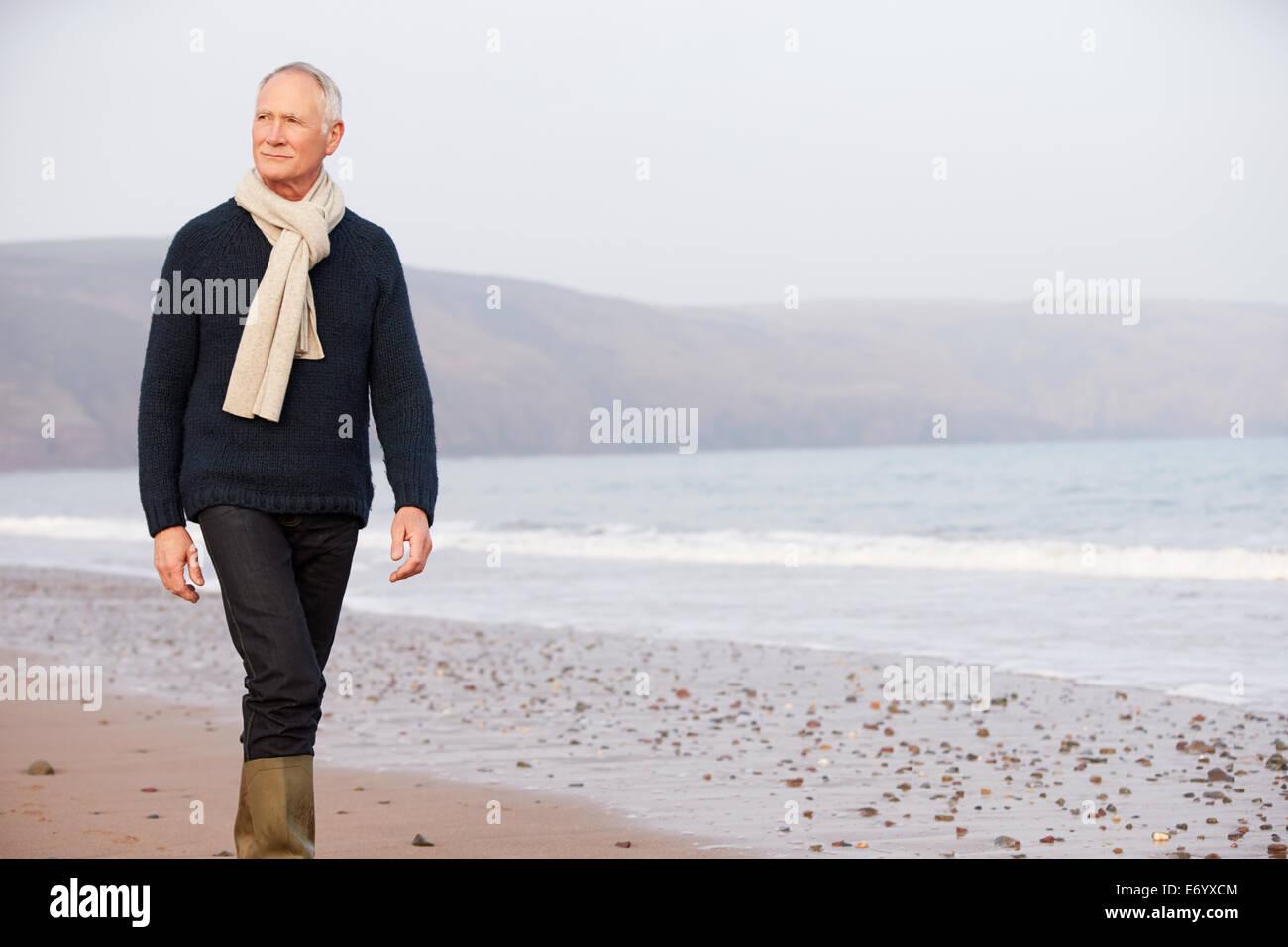 Senior Man Walking Along Winter Beach - Stock Image