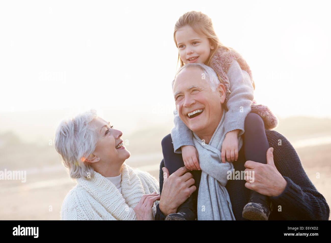 Grandparents And Granddaughter Walking On Winter Beach - Stock Image