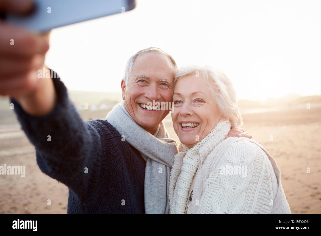 Senior Couple Standing On Beach Taking Selfie - Stock Image