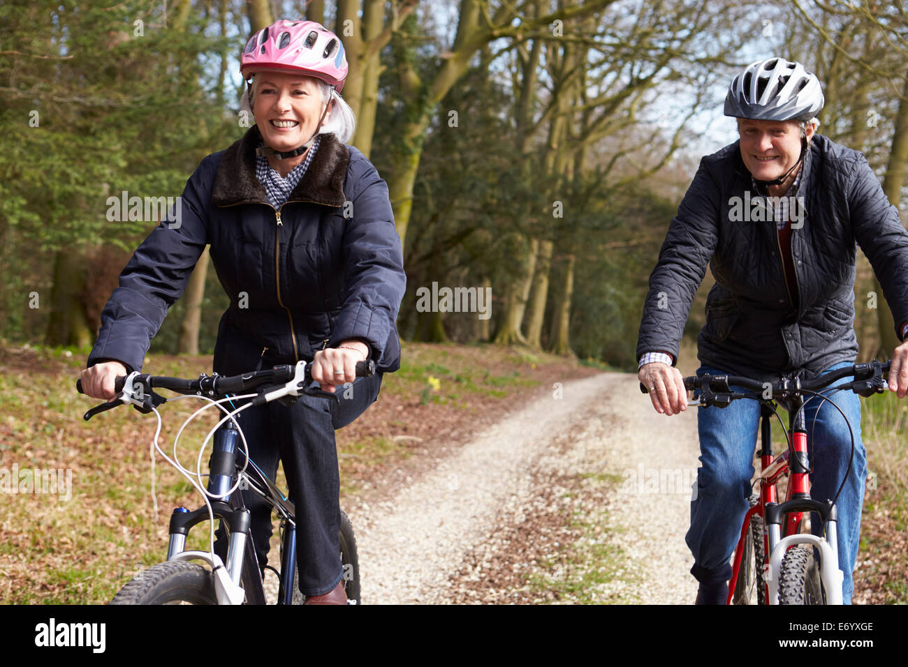 Couple Cycling Along Urban Street Together - Stock Image