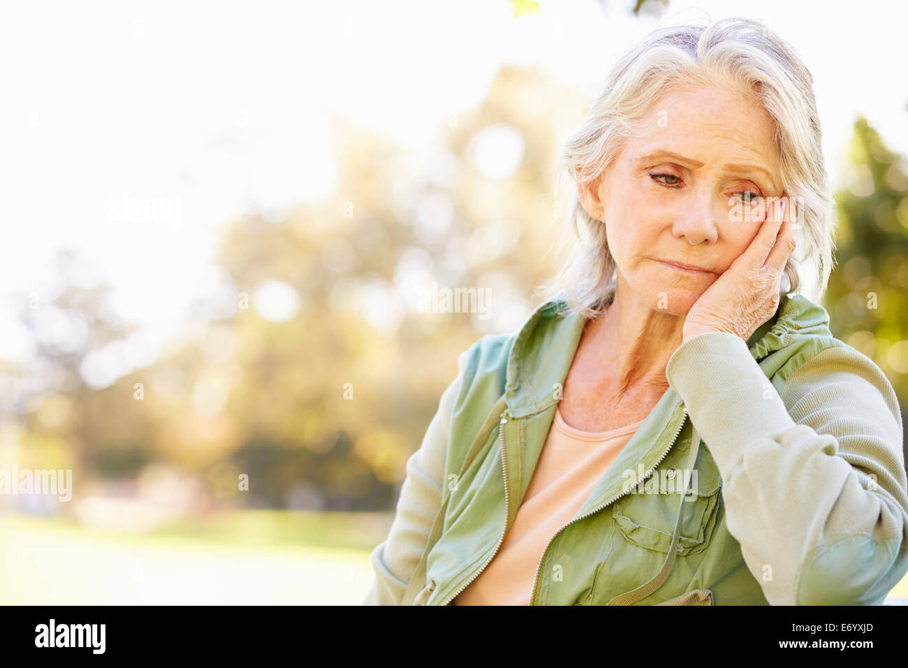 Depressed Senior Woman Sitting Outside - Stock Image