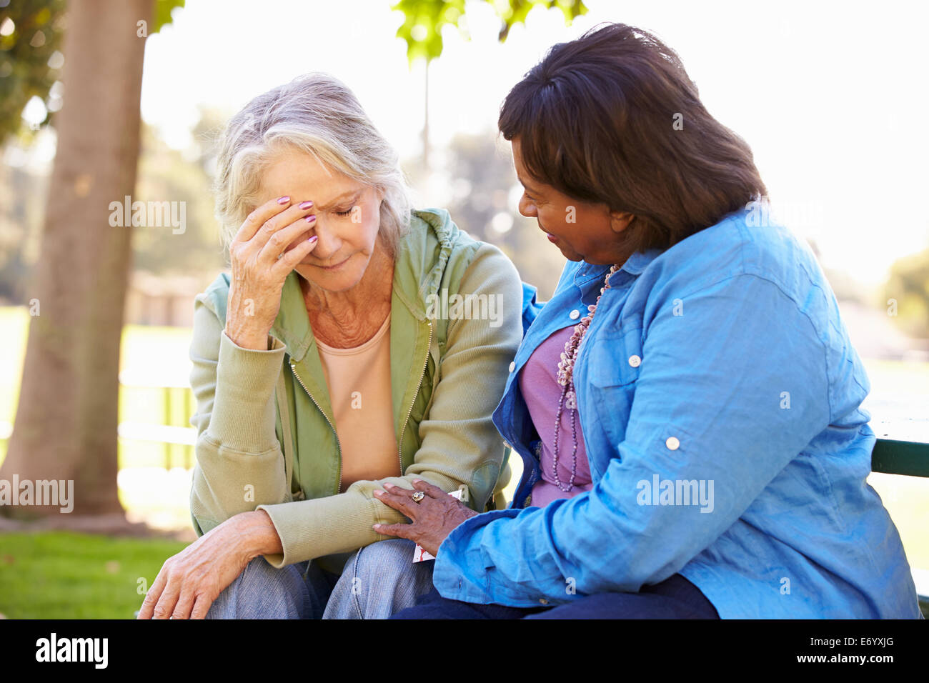 Woman Comforting Unhappy Senior Friend Outdoors - Stock Image