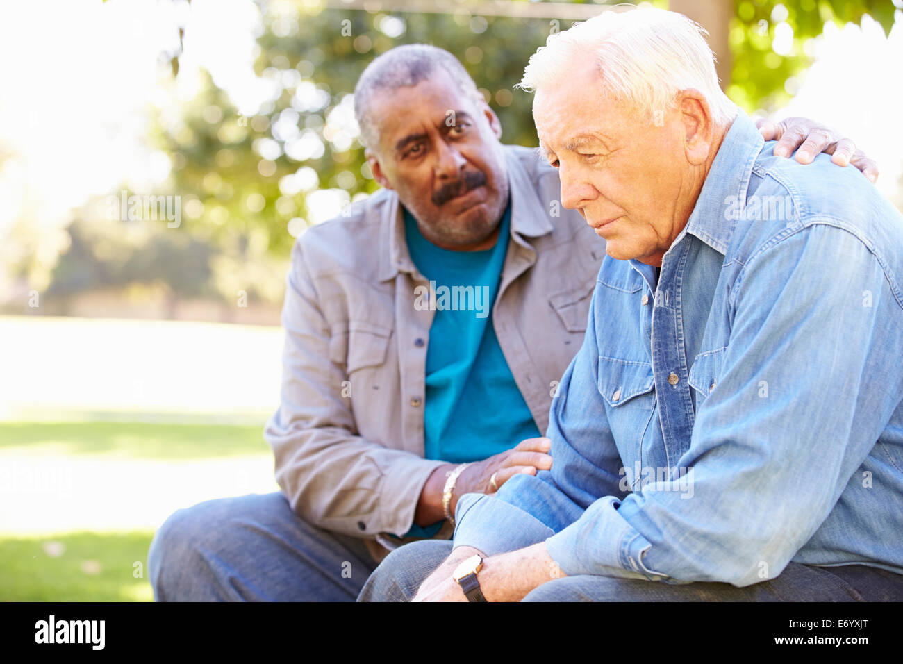 Man Comforting Unhappy Senior Friend Outdoors - Stock Image