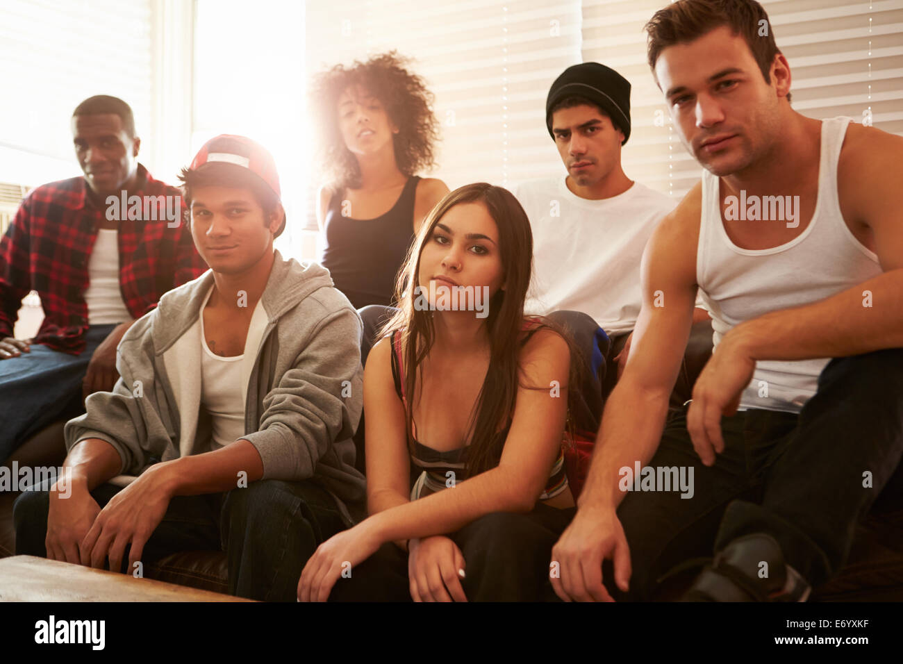 Portrait Of Gang Members Sitting On Sofa In House - Stock Image