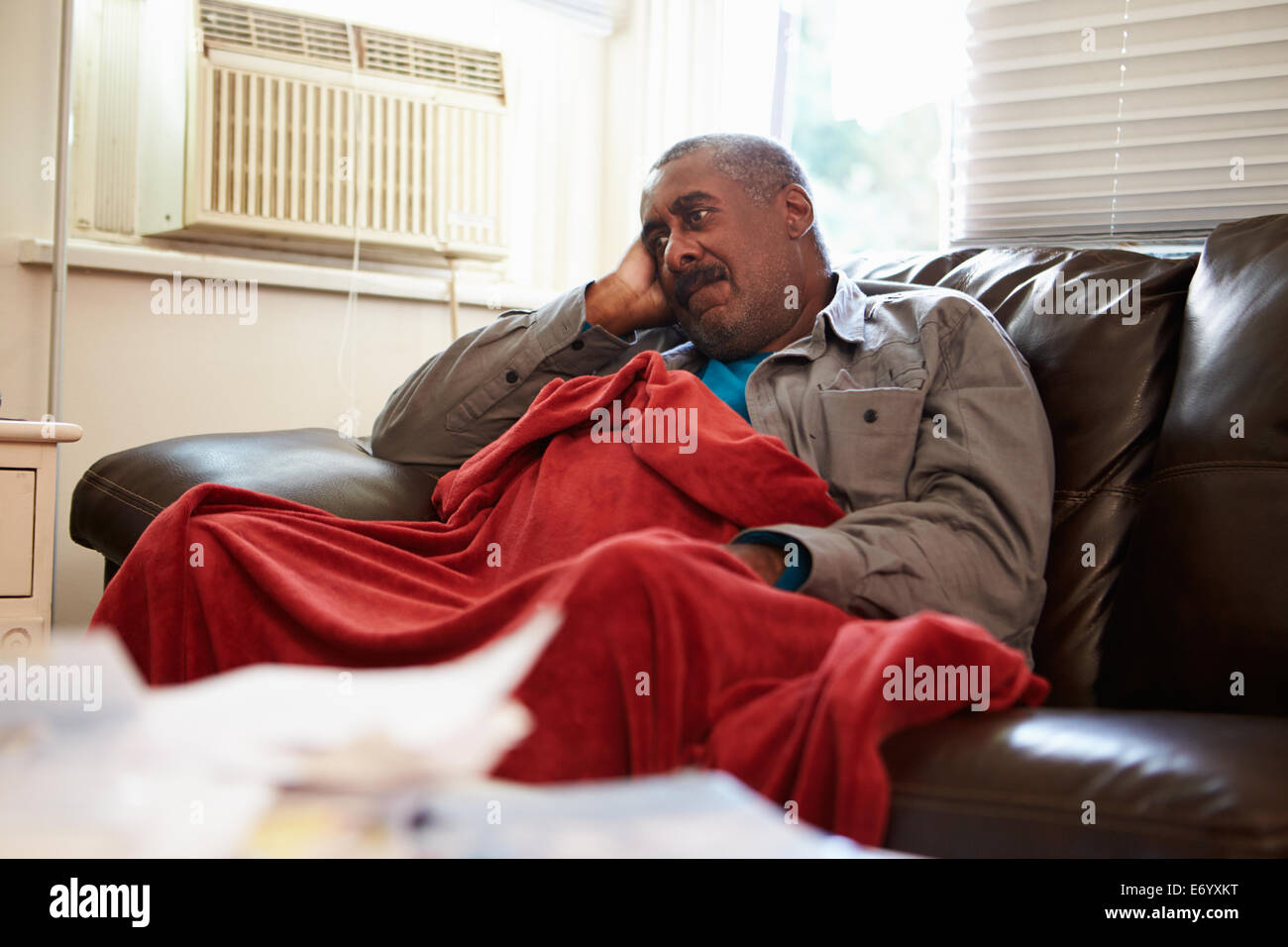 Senior Man Trying To Keep Warm Under Blanket At Home - Stock Image