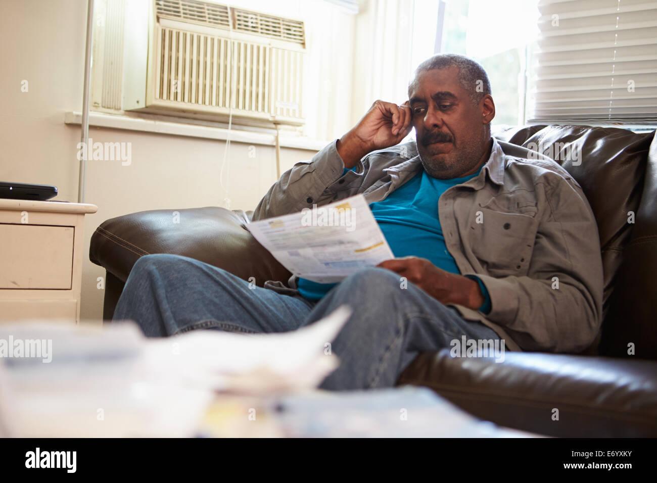 Worried Senior Man Sitting On Sofa Looking At Bills - Stock Image